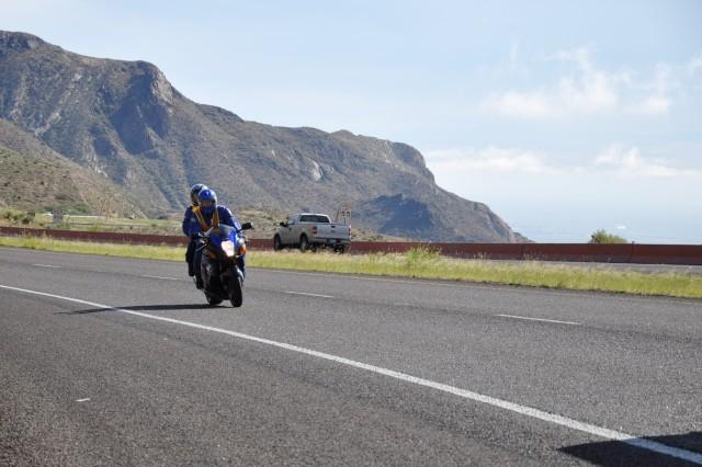 "Tom McFarland riding his Suzuki Hayabusa motorcycle with coworker Grace Joralmon as a passenger."""