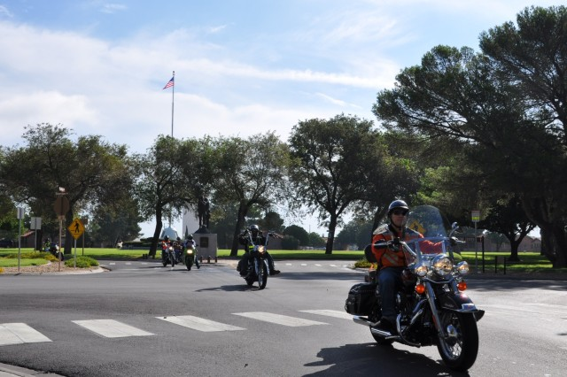 """Col. Fetterman leading a procession of FFID motorcyclists in front of the """"First to Strike"""" Air Defense statue by Pershing Gate."""""""