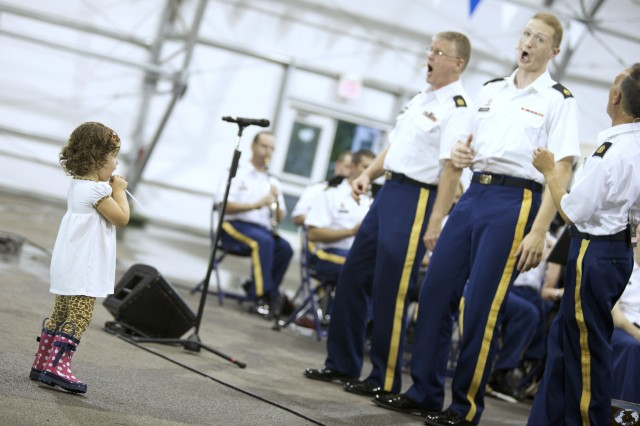 Two-year-old Grace Kiamie enjoys The U.S. Army Field Band's barbershop quartet, Soundoff, up close and personal. Hundreds of concertgoers, including children, were entertained Aug. 22 as part of the summer concert series on Fort Meade.