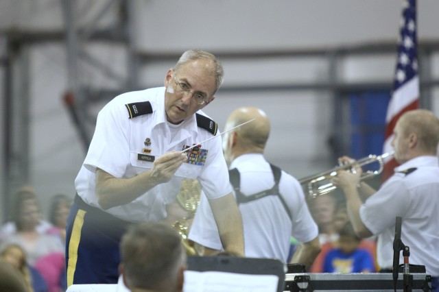 """Chief Warrant Officer Gordon K. Kippola conducts """"The Cool School,"""" a song arranged by Command Sgt. Maj. Loran McClung who also plays lead sax for the song. The alumni concert at the Fort Meade Pavilion Aug. 22 marks McClung's final performance as an active member of the Concert Band."""