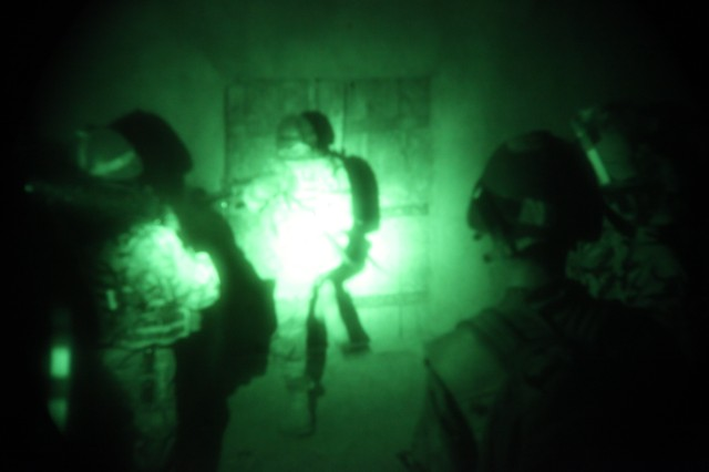 Coalition forces alongside Afghan commandos kick down a door during an air assault mission in the Paktika province of Afghanistan, Aug. 14.
