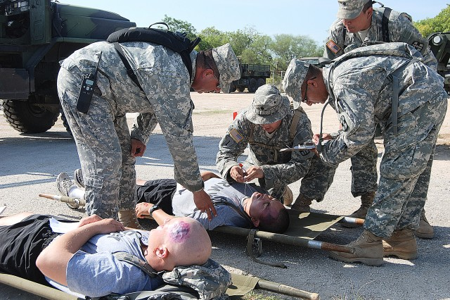 Soldiers with various mock combat injuries are triaged outside the 228th Combat Support Hospital and Patient Administrative Division personnel remove any effects that need to be taken from the patient, such as weapons before they can be brought into the Emergency Medical Treatment section during the exercise Aug. 12 at Fort Sam Houston.