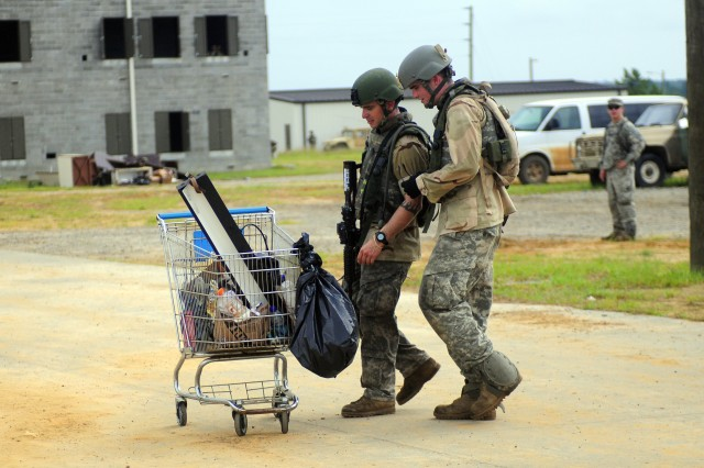 """Two """"Iraqi"""" Soldiers investigate a shopping cart for explosives during ORS II, Aug. 15."""