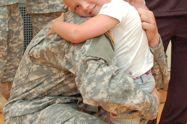Pvt. Scott Mix, a student, hugs his niece Aug. 26, 2009, at the Muscatatuck Urban Training Center, Ind., following the dedication of the National Guard Patriot Academy here. While at the academy, the student-Soldiers receive a nationally-accredited diploma through online courses offered through Liberty University.