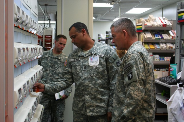 The Commanding General of Fort Campbell, KY, Maj. Gen. John F. Campbell and his wife Anne visited Blanchfield Army Community Hospital (BACH) Aug. 27.  They received a brief from BACH's hospital commander Col. John P. Cook and toured clinical areas.  Pharmacy non commissioned officer in charge Sgt. 1st class Kevin Dennis shows Maj. Gen. Campbell how outpatient pharmacy prescription are filled. BACH pharmacists and pharmacy technicians work side by side with robotics to provide safe and accurate comprehensive pharmaceutical services to patients.