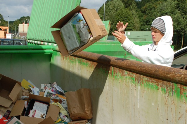 Aaron Warren, DPW Summer Hire employee at Schinnen, tosses a box of paper recyclables into one of the large bins at Schinnen's sort center.