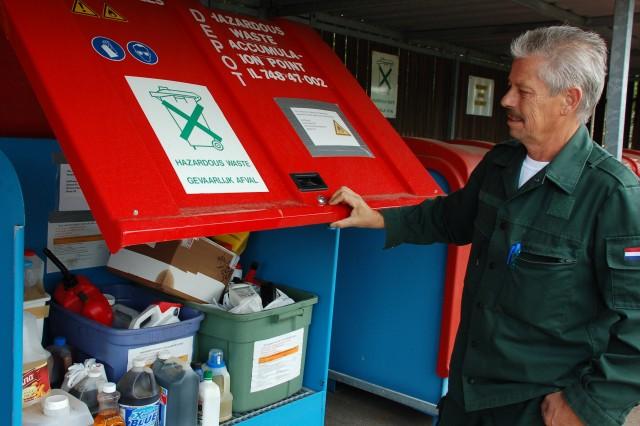 Alfredo Dorio, Schinnen's sort center manager, raises the protective cover on one of the hazardous material bins.