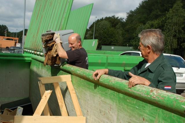 Doug Housel (left) dumps wood pieces into a recycle bin as Alfredo Dorio, Schinnen's sort center manager, watches.