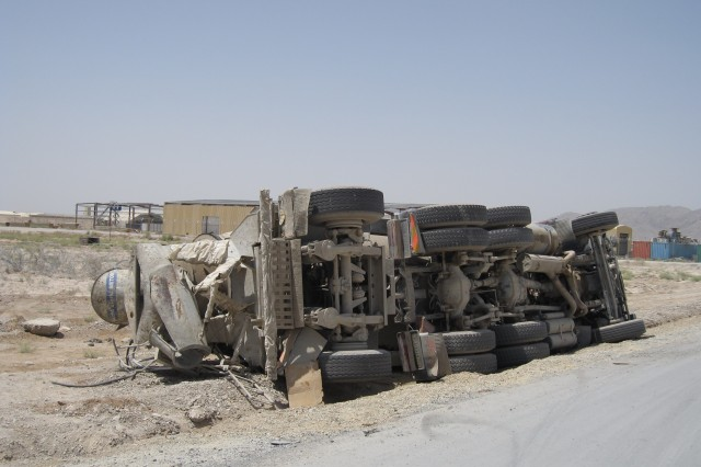 A cement truck that lost control and rolled over Aug. 21 rests on its side by a road at Kandahar Airfield, Afghanistan.  Master Sgt. Joseph Oswald, an Army Reservist from Cincinnati, Ohio, was the first on the scene and rendered first aid to the Afghan driver, who was taken by ambulance to the coalition hospital.