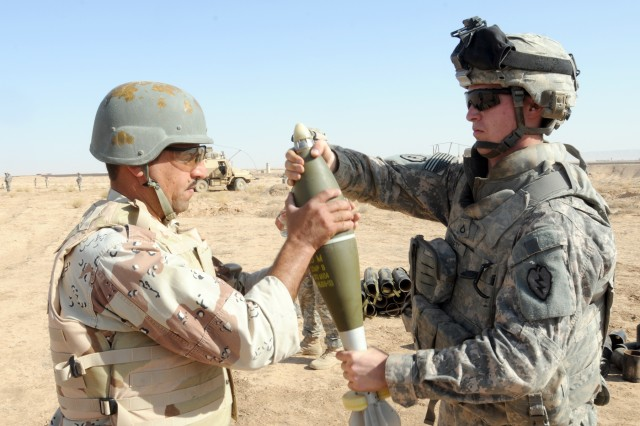 CONTINGENCY OPERATING BASE SPEICHER, TIKRIT, Iraq - Pfc. Cody Haggett, 21, of Levant, ME, mortar man, Headquarters and Headquarters Company, 2nd Battalion, 27th Infantry Regiment, 3rd Infantry Brigade Combat Team, 25th Infantry Division hands a 120 mm mortar round to a 4th Iraqi Army Division, 48th Brigade, Light Mortar Battery Soldier to be loaded and fired during a live fire mortar training exercise at Al Siniyah Air Base in Bayji, Aug. 18.