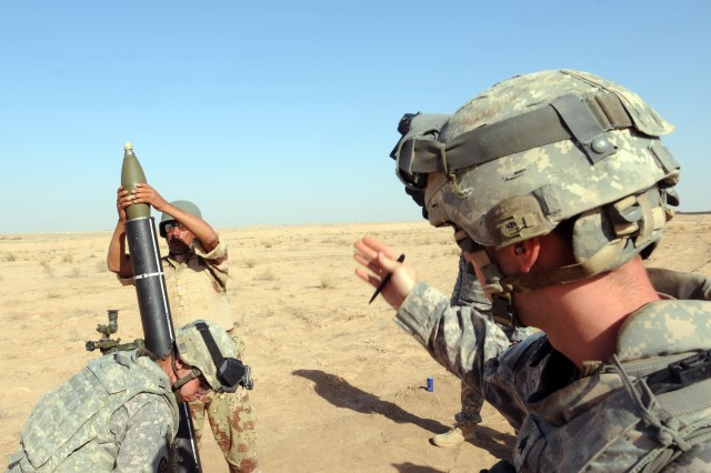 CONTINGENCY OPERATING BASE SPEICHER, TIKRIT, Iraq - Sgt. Steven Tremper, 23, of Warren, MI, mortar man, Headquarters and Headquarters Company, 2nd Battalion, 27th Infantry Regiment, 3rd Infantry Brigade Combat Team, 25th Infantry Division gives a command to an Iraqi Soldier to load a 120 mm mortar round during a live fire exercise where 57 Soldiers of 4th Iraqi Army Division, 48th Brigade, Light Mortar Battery completed their final portion of a three-week basic mortar training event at Al Siniyah Air Base in Bayji, Aug. 18.