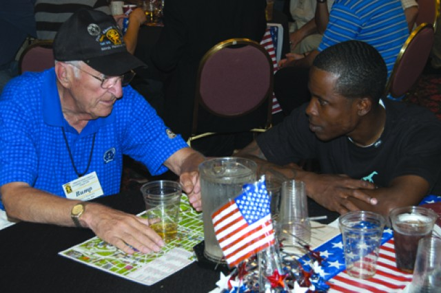 """William """"Bump"""" Boehmke (left), a veteran of the 509th Parachute Infantry Battalion from World War II, visits with the Staff Sgt. Evrod Folkes, 1st Bn (Abn), 509th Inf Reg during the 509th PIB reunion Aug. 23 in San Antonio, Texas."""