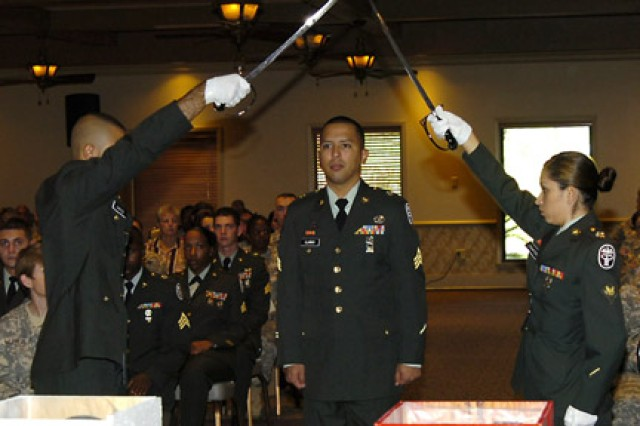 Sgt. Michael Llanas passes under a sabre arch during an NCO induction ceremony held at the Warrior Community Center Aug. 12.