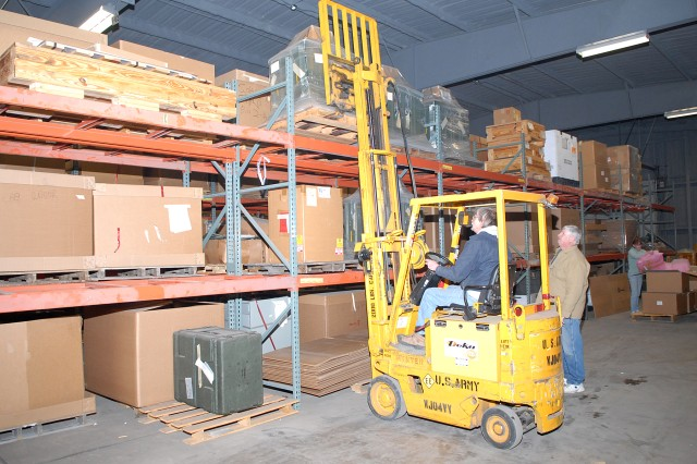 Thomas Becker (right), CECOM Life Cycle Management Command team leader, helps Thomas Damski, material handler, use a forklift to remove UNIDENT items from storage.