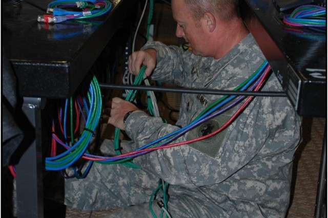 Sgt. 1st Class Mark A. Nelis, a U.S. Army South system administrator, sets up network cables of the Deployable Joint Command and Control system here July 8. DJC2 serves as the information hub for Army South, joint sister services, and partner nation coalition personnel to plan and conduct operations during the Fuerzas Aliadas PANAMAX 2009 exercise. (Photo by Kristen S. Darm, U.S. Army South Public Affairs Office)