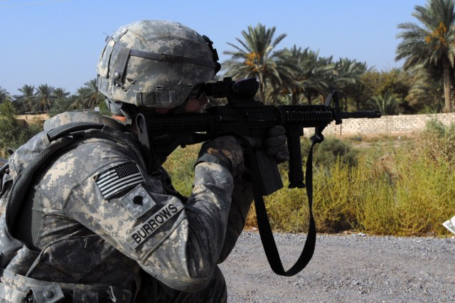 CAMP TAJI, Iraq- Pennsboro, W. Va. native, Spc. Christopher Burrows, a forward observer assigned to Headquarters and Headquarters Battery, 1st Battalion, 82nd Field Artillery Regiment, 1st Brigade Combat Team, 1st Cavalry Division, provides perimeter security during a dismounted support operation with Iraqi Federal Police in Taji Aug. 23.