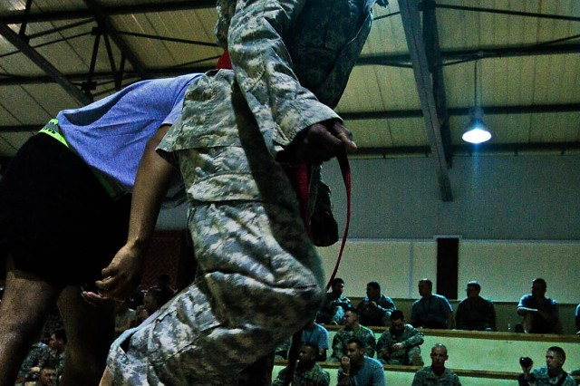 """CAMP TAJI, Iraq-Spc. De Andre Jackson, from San Francisco, a generator mechanic for Headquarters Support Company, 615th Aviation Support Battalion, 1st Air Cavalry Brigade, 1st Cavalry Division, steps into the ring before winning a combatives match during a tournament held by the 10th Sustainment Brigade, Aug. 29, Camp Taji, Iraq. Jackson would go on to place fourth in his weight class. """"(I'm) happy that I've done my best, but what made me mad was that I had two or three submissions in and I didn't hold on to them,"""" said Jackson of his final fight. """"Next time I won't be passive aggressive, but aggressive aggressive."""""""