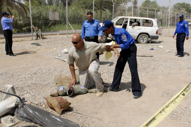An Iraqi police officer removes a mock suspect from the secured scene of a mock car bomb explosion. The suspect is an instructor at the new Police Center of Excellence located on Camp Liberty, Iraq. The Iraqi police officers were participating in practical exercise prior to their graduation from the center which teaches them enhanced skills in evidence gathering and documentation.