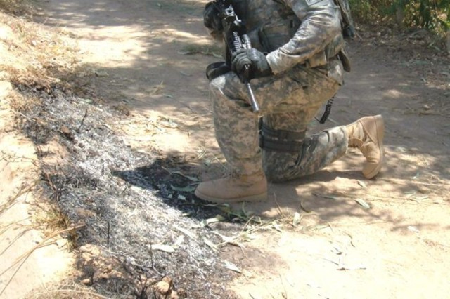 Sgt. James Reed, from the 266th Military Police Company, stops to check a burn mark he discovered while on a foot patrol near Joint Base Balad, Iraq. Such burn marks in the ground are an indication of a possible rocket-launch site