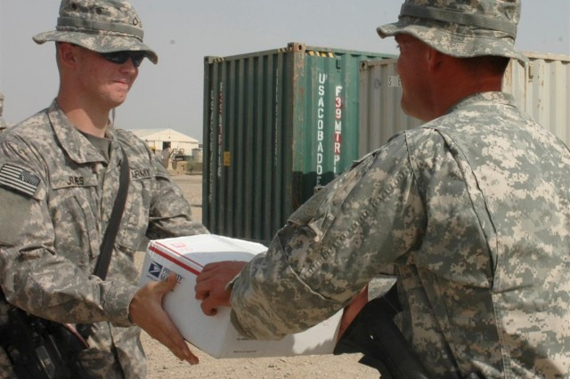 2nd Battalion, 162nd Infantry Regiment, Convoy Commander, Staff Sgt. Brian Chytka from Albany Ore., hands Private 1st Class Casey Jones a care package Aug. 18 that was sent by 4th graders from Albany Christian School who the Soldiers visited prior to coming on their deployment.