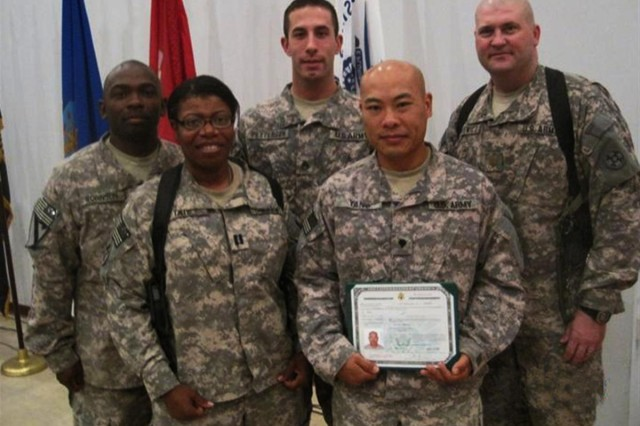 Spc. Vilay Yang displays his U.S. Citizenship certificate, given to him during a ceremony held Aug. 6 at Camp Arijfat, Kuwait