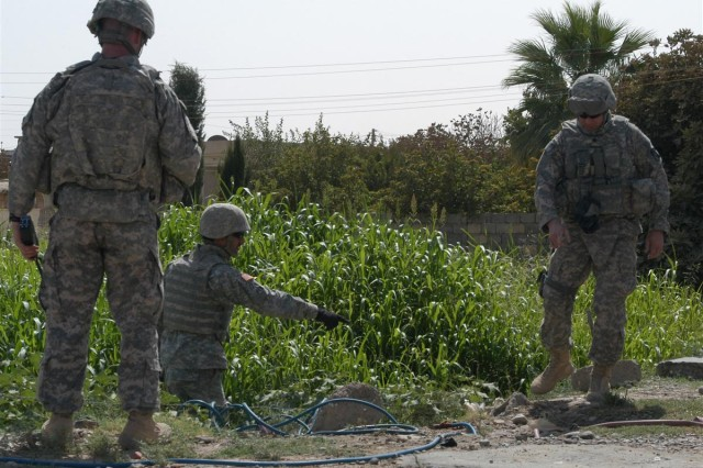 An Iraqi interpreter, standing waist deep in lush grass, observes with Lt. Col. William B. Smith Jr., the Q-West, Iraq, mayor, an unauthorized pipe tapped into the 16-inch pipeline supplying water to Q-West during a recent leader's reconnaissance of the pipeline in the Ninawa Province of northern Iraq.