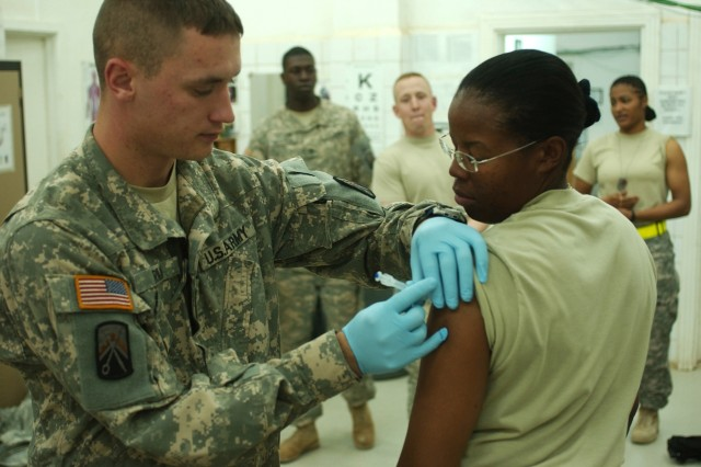 In this file photo, Spc. Joshua Ryan, a medic with the 16th Special Troops Battalion, 16th Sustainment Brigade, administers the influenza vaccine to Staff Sgt. Jacqueline Atkins at the troop medical clinic at Contingency Operating Base Q-West, Iraq, Nov. 10 of 2008. On Sept. 1, the Department of Defense announced that all troops will receive the H1N1 vaccination.