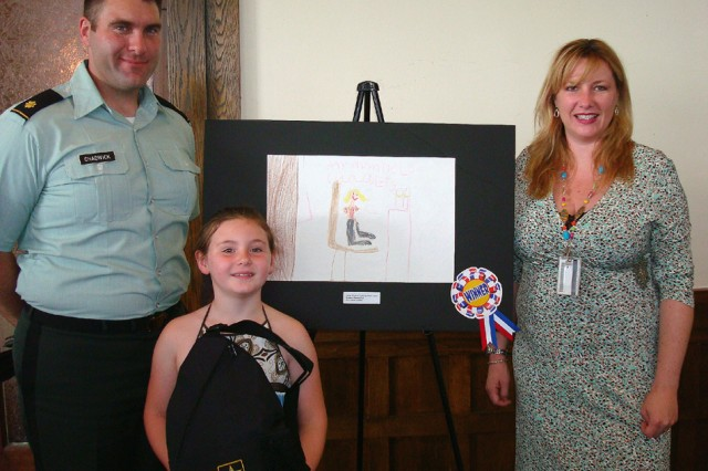 Emma Chadwick, front, stands in front of her poster that won the 'Real Women' poster contest. She is accompanied by her parents, Maj. Douglas Chadwick and Heather.