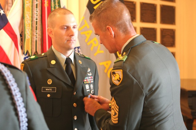 Staff Sgt. John White is awarded the Army Achievement Medal from Command Sgt. Maj. Martin Wells during the NCO/Soldier of the Quarter Award ceremony Monday in Cullum Hall. White and Spc. William Powers, both military policeman with the U.S. Army Garrison MP Co., were recognized for the 3rd Quarter of Fiscal Year '09. In addition to the AAM, both received a framed print, a plaque and one-year membership from AUSA-West Point Chapter, and a Directorate of Family and Morale, Welfare and Recreation gift certificate for a dinner and movie. White and Powers will compete against the previous winners of the quarterly competitions at the upcoming NCO/Soldier of the Year Board.