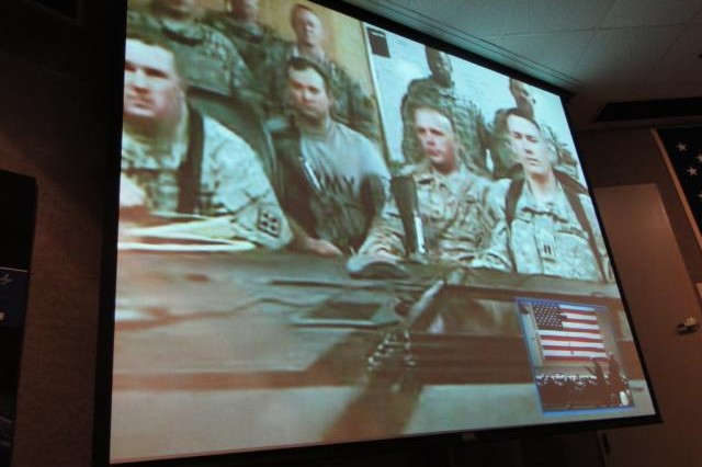 Soldiers from the 375th Engineer Company watch intently as their families receive blue star banners during the Aug. 22 Blue Star Service Banner program held in the auditorium at Lockheed Martin in Cummings Research Park. The company arranged for the video teleconference, which was the first time the technology has been used in Huntsville to connect a large number of deployed Soldiers with their families.