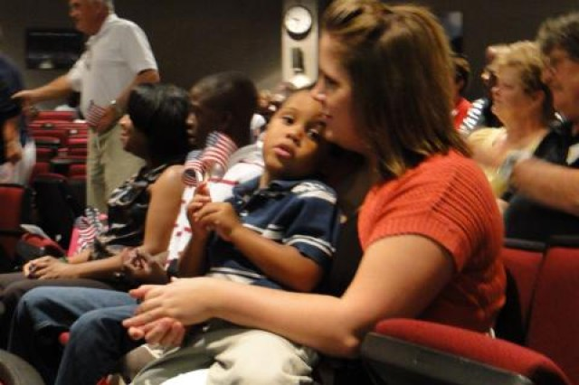 Brandon Johnson, 3, sits quietly in the arms of family friend Casey Atkinson during the Blue Star Service Banner program for families of the Reserve's 375th Engineer Company on Aug. 22. Brandon is the son of Sgt. Robert Johnson, who is deployed in Iraq with the 375th.