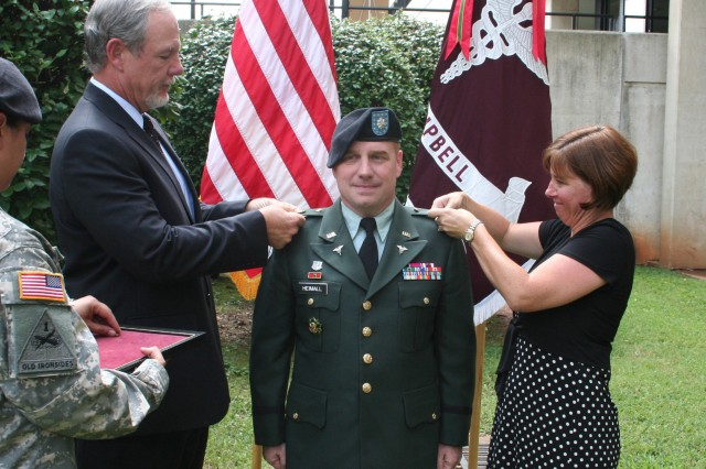 Col. Michael S. Heimall, BACH's deputy commander for administration, stands at attention as his wife Lynda and Mr. William H. Thresher, director of TRICARE Regional Office South, pin on new Colonel rank Sept. 3 in front of BACH on Fort Campbell,