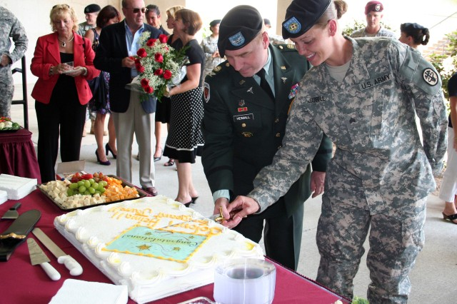 """Col. Michael S. Heimall, Blanchfield Army Community Hospital (BACH) deputy commander for administration, and Sgt. Crystal Jarrell, combat medic at BACH, slice into their cake at their shared promotion ceremony celebration Sept. 3 at BACH on Fort Campbell, Ky.  In honor of the Year of the Non Commissioned Officer, Heimall said, """"I cannot think of a better Soldier to share my promotion ceremony with than Sgt. Jarrell."""""""