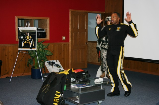 U.S. Army Golden Knights Tandem Team Leader, Sgt. 1st Class Michael Elliott, shows the tandem jumpers the proper exit from the aircraft, as part of his class of instruction.
