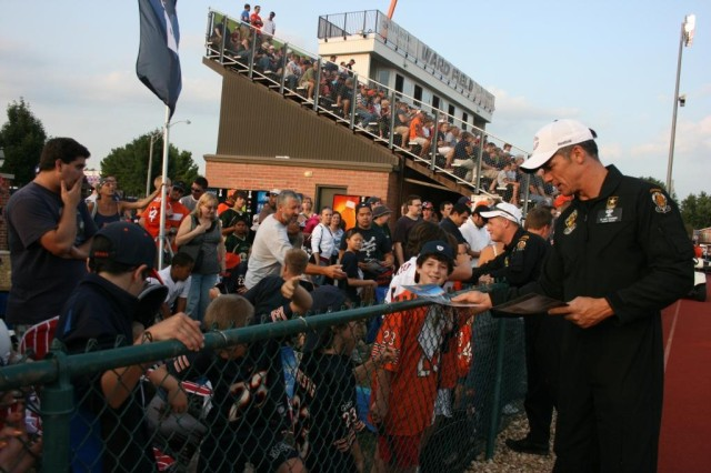 Sgt. 1st Class Kurt Isenbarger, hands out some of his Golden Knight posters to some of the thousands of fans after his team jumped into a pre-season game at the Chicago Bears Training Camp, Bourbonnais, IL.