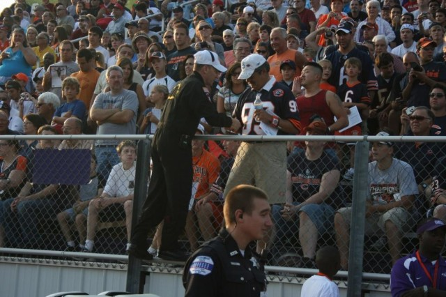 Sgt. 1st Class Dave Herwig climbs the fence to appease some of the thousands of fans at he Chicago Bears Training Camp pre-season game, after his team jumped into the Olivet Nazarene College Football Stadium.