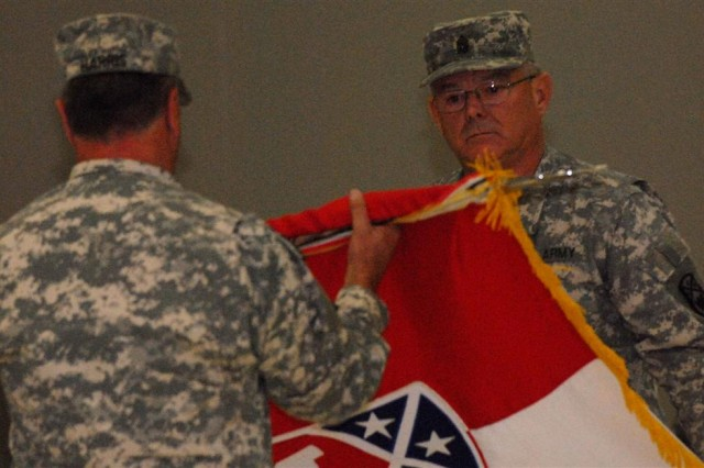 Command Sgt. Maj. Charles G. Hudson, the brigade command sergeant major with the 194th Engineer Brigade, and Brig. Gen. Robert A. Harris, the brigade commander for the 194th, unveil the unit flag during a transfer of authority ceremony Aug. 29 here at Joint Base Balad, Iraq.