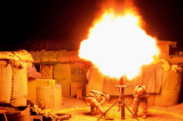 Spc. Patrick Wilson, left, and Spc. Evaristo Garcia fire a 120 mm high-explosive mortar round during an illumination exercise on Forward Operating Base Mizan, Afghanistan, Sept. 2, 2009. Wilson and Evaristo are assigned to Company A, 1st Battalion, 4th Infantry Regiment.