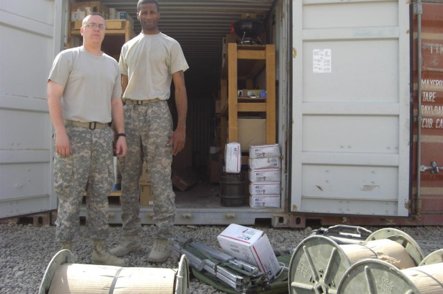 Sgt. 1st Class Michael Tiberi and Staff Sgt. Stephen Murphy work to identify excess and unusable property that can be sent to units or disposed of in support of the drawdown of forces and equipment from Iraq.