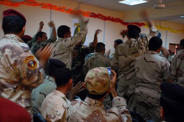 Iraqi Army Bomb Disposal School Level IV graduates celebrate while singing the Iraqi Army warrior song, Aug. 26, in Besmaya, Iraq.