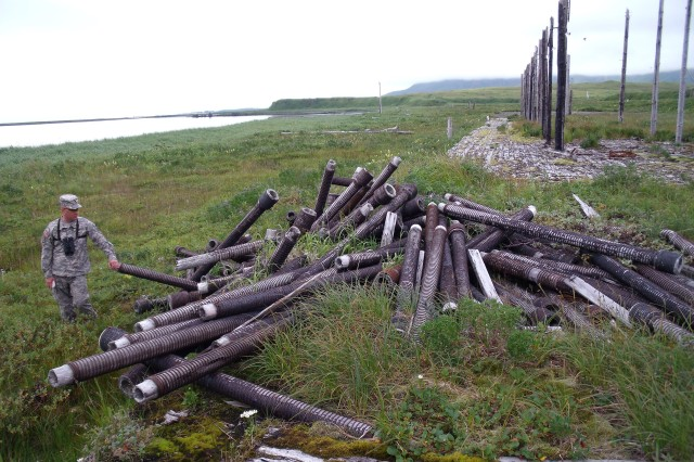 Master Sgt. David Crandall, 6th Engineer Battalion, investigates a pile of wooden pipes near a beach on Attu Island Aug. 15. The beach may have been used as a loading dock for the Japanese forces that seized the island for a year-and-a-half during World War II.