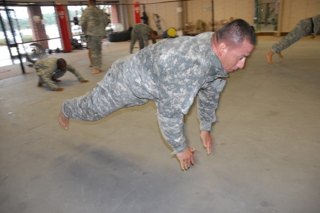 A member of the Fort Jackson combatives team leaps into the air during warm-ups before a team workout. The team is training to compete in the Army Combatives Tournament at Fort Benning, Ga., Sept. 18-20.