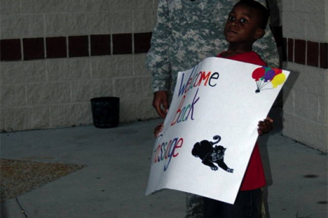 Tyshon Stewart, 7, holds a sign of welcome at the main entrance of Mary Passage as mom, Sgt. 1st Class Nekena Smith of the Eustis WTU, looks on.