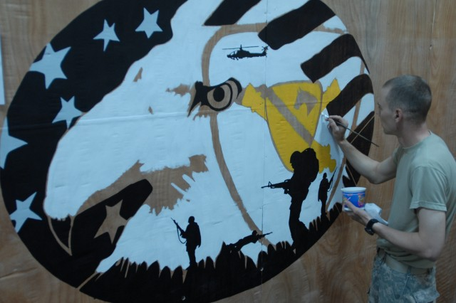 """CAMP TAJI, Iraq - """"I figured I'd design a mural because this wall was blank and I wanted to paint something that represented my unit,"""" explained Perry, Iowa native, Pfc. Corey Smith, a personal security detachment driver assigned to Headquarters and Headquarters Battery, 1st """"Dragon"""" Battalion, 82nd Field Artillery Regiment, 1st Brigade Combat Team, 1st Cavalry Division, while he added some shading to the mural at the """"Dragon"""" Tactical Operations Center on Camp Taji, Sept. 5. Smith designed the mural to include the 1st Cavalry Division patch, artillery crossed cannons, an Apache helicopter, an M109A6 howitzer, an eagle, and Soldiers on a dismounted patrol."""