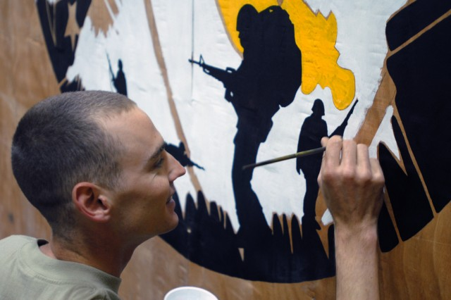 """CAMP TAJI, Iraq - """"I've always loved art,"""" said Perry, Iowa, native Pfc. Corey Smith, a personal security detachment driver assigned to Headquarters and Headquarters Battery, 1st """"Dragon"""" Battalion, 82nd Field Artillery Regiment, 1st Brigade Combat Team, 1st Cavalry Division, as he added his personal touch to a blank wall in the """"Dragon"""" Tactical Operations Center on Camp Taji, Sept. 5."""