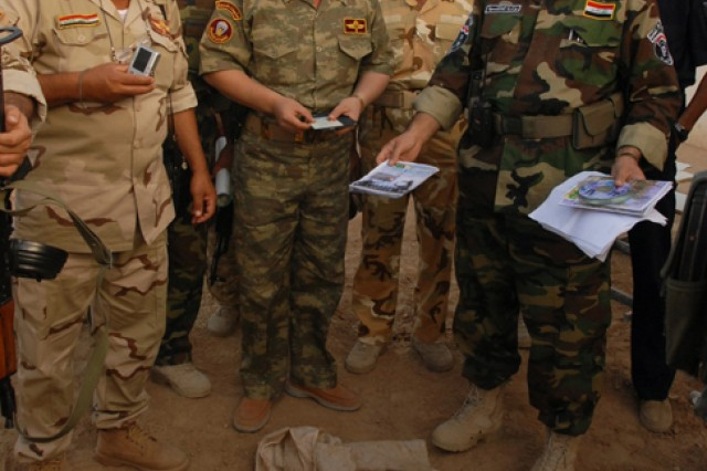 """Brigadier General Sarhat (right), the outer city police chief for Kirkuk province, examines insurgent propaganda found during operation """"Enforce the Law VI"""" in the Rashaad Valley in Kirkuk province, Iraq, Sept. 2. The operation was a joint venture between Iraqi Army and Iraqi Police, and it was the first operation in this area to be completely planned and executed by Iraqi Security Forces."""