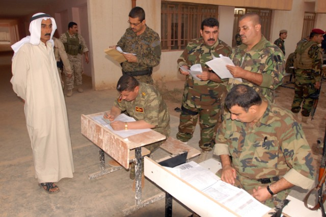 """Members of the Iraqi Security Forces examine a villager's paperwork during operation """"Enforce the Law VI"""" in the Rashaad Valley in Kirkuk province, Iraq, Sept. 2. The village was allowed to go back to his home freely after the ISF confirmed his name was not on any wanted list."""