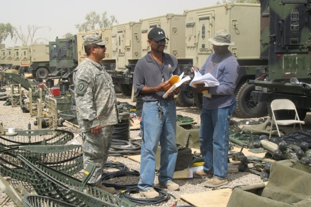 Mike Calhoun, 51st Signal Battalion noncommissioned officer (left), oversees inventory of equipment at Balad, Iraq.