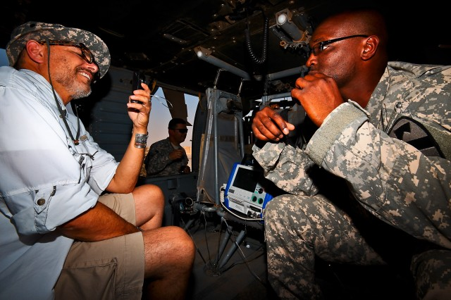 CAMP TAJI, Iraq-While sitting in a UH-60 Black Hawk medevac helicopter, Sgt. 1st Class Cleron (right) Washington, from Walter Berg, S.C., the flight medic noncommissioned officer in charge for Company C, 2nd Battalion, 227th Aviation Regiment, 1st Air Cavalry Brigade, 1st Cavalry Division, Multi-National Division - Baghdad, gives actor Joe Pantoliano (left) an idea of how a medevac unit operates, Camp Taji, Iraq, Sept. 5. Joe, who lives with depression, came to here to promote awarness of mental illness and various ways to deal with it.