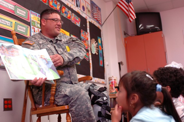 Pfc. Micheal Sparling shows photos as he reads to  Alexis Thompson and Eric Torres, pre-kindergarten students at Maxdale Elementary School in Killeen, Texas, Sept. 8.Four 'Greywolf' Soldiers spent two hours with pre-K students reading various children's books in support of the school's literacy day. Sparling is a signal intelligent analyst from Port Huron, Mich., with Rear Detachment, 3rd Special Troops Battalion, 3rd Heavy Brigade Combat Team, 1st Cavalry Division.